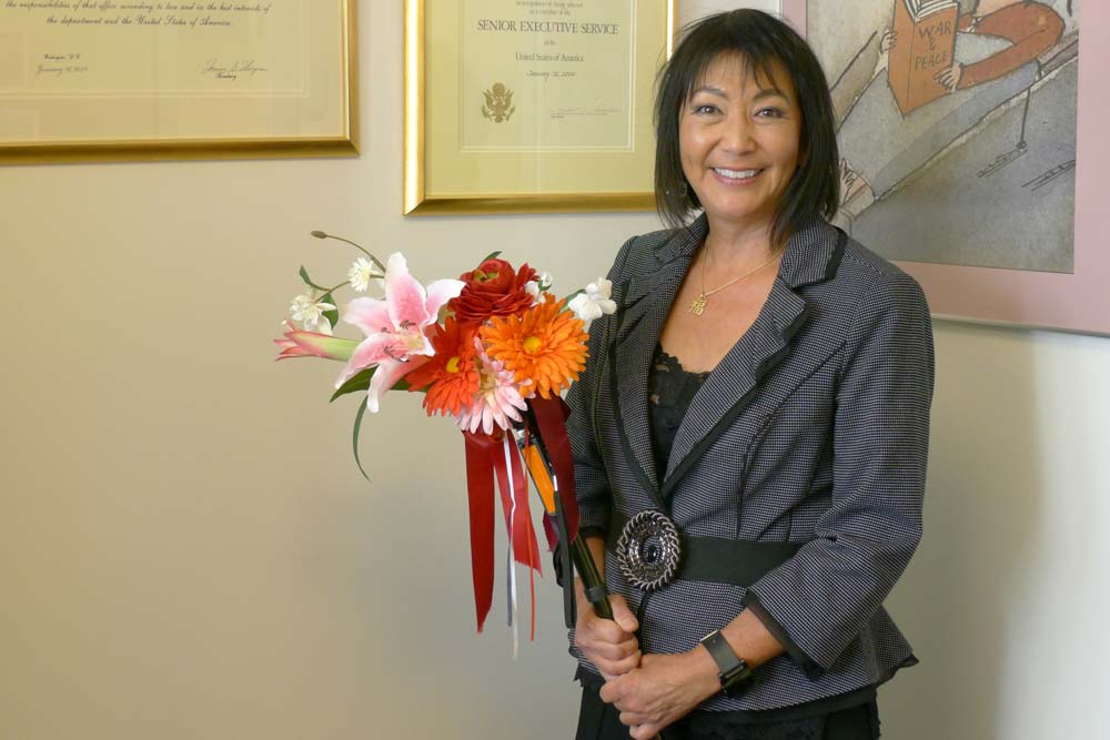 Dr. Charlotte Yeh in her AARP office, proudly holding her colorfully decorated cane.